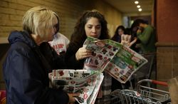 ** FILE ** Katie Stroh, left, and Gretchen Burkhardt look at catalogs while waiting outside a Kmart store on Thursday, Nov. 28, 2013, in Anaheim, Calif. Instead of waiting for Black Friday, which is typically the year's biggest shopping day, more than a dozen major retailers opened on Thanksgiving day this year. (AP Photo/Jae C. Hong)