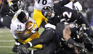 Pittsburgh Steelers running back Le'Veon Bell (26) loses his helmet after a collision as he tries to score a touchdown in the second half of an NFL football game against the Baltimore Ravens, Thursday, Nov. 28, 2013, in Baltimore. Bell left the field with an injury and the touchdown attempt was no good. (AP Photo/Gail Burton)