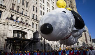 A giant Snoopy balloon passes a balcony of spectators during the 87th Annual Macy's Thanksgiving Day Parade, Thursday, Nov. 28, 2013, in New York. After fears the balloons could be grounded if sustained winds exceeded 23 mph, Snoopy, Spider-Man and the rest of the iconic balloons received the all-clear from the New York Police Department to fly between Manhattan skyscrapers on Thursday. (AP Photo/John Minchillo) **FILE**