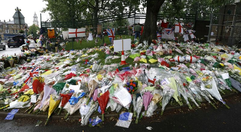** FILE ** This Tuesday, May 28, 2013, file photo shows floral tributes at the scene where 25-year-old soldier of the Royal Regiment of Fusiliers Lee Rigby was attacked and killed, near Woolwich Barracks in London. (AP Photo/Kirsty Wigglesworth)