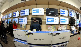 Shoppers look at televisions at a Best Buy store late in the evening on Thanksgiving Day, Thursday, Nov. 28, 2013, in Dunwoody, Ga. Instead of waiting for Black Friday, which is typically the year's biggest shopping day, more than a dozen major retailers opened on Thanksgiving this year. (AP Photo/David Tulis)