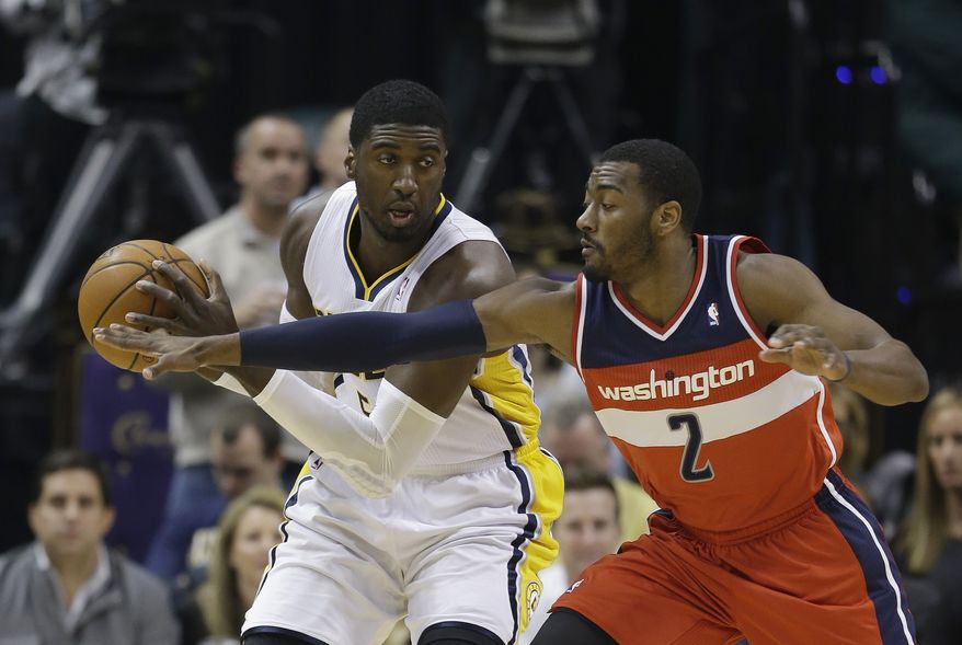 Indiana Pacers' Roy Hibbert, left, is defended by Washington Wizards' John Wall (2) during the first half of an NBA basketball game Friday, Nov. 29, 2013, in Indianapolis. (AP Photo/Darron Cummings)