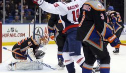 Washington Capitals center Nicklas Backstrom (19) celebrates after scoring a goal with less than a minute left to play in the third period to tie the game as New York Islanders goalie Anders Nilsson (45) kneels and teammate Travis Hamonic (3) skates away during an NHL hockey game in Uniondale, N.Y., Saturday, Nov. 30, 2013. Capitals won 3-2 in overtime.  (AP Photo/Paul J. Bereswill)