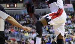 Washington Wizards point guard John Wall (2) leaps to save the ball against the Atlanta Hawks during the first half of an NBA basketball game, Saturday, Nov. 30, 2013, in Washington. (AP Photo/Nick Wass)
