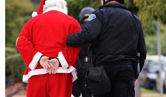 Wal-Mart protester Karl Hilgert, dressed as Santa Claus, is led away after being arrested for failure to disperse after sitting down with nine other protesters in the middle of an intersection on Friday, Nov. 29, 2013, in Ontario, Calif. A labor group and supporters used the Black Friday shopping period for a demonstration over wages and working conditions at Wal-Mart. The San Bernardino Sun reports that more than 100 demonstrators gathered near the Wal-Mart in Ontario at 6 a.m. (AP Photo/The Inland Valley Daily Bulletin, Will Lester) MANDATORY CREDIT