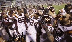 Virginia Tech linebacker Tariq Edwards (24) holds the Commonwealth Cup as he and his teammates celebrate their 16-6 win over Virginia after an NCAA college football game in Charlottesville, Va., Saturday, Nov. 30, 2013. (AP Photo/Steve Helber)