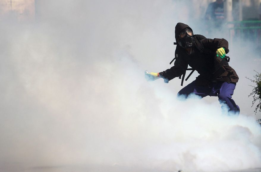 A protester gets ready to throw back a tear gas canister fired by riot police in Bangkok. Police clashed with anti-government mobs trying to force their way into the prime minister's office complex and Bangkok's police headquarters Sunday. The protesters want Prime Minister Yingluck Shinawatra to resign. (Associated Press)