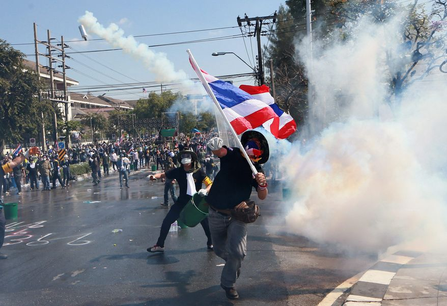 Back and Forth: A protester throws back a tear gas canister fired by riot police in Bangkok as Thailand's political crisis deepens, raising fears of prolonged instability in one of Southeast Asia's biggest economies. (ASSOCIATED PRESS PHOTOGRAPHS)