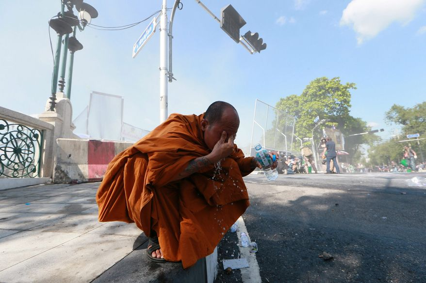 Danger: A Buddhist monk washes tear gas from his eyes after protesters clash with riot police.