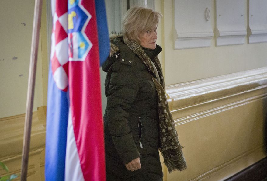 A voter walks past the Croatian flag at a polling station in Pula, Croatia, on Sunday, Dec. 1, 2013, as the nation votes in a referendum that could ban gay marriages. Conservative groups, backed by the Roman Catholic Church, demanded that the country's constitution define matrimony as a union of a man and a woman. The issue has divided the European Union's newest member nation. (AP Photo/Darko Bandic)