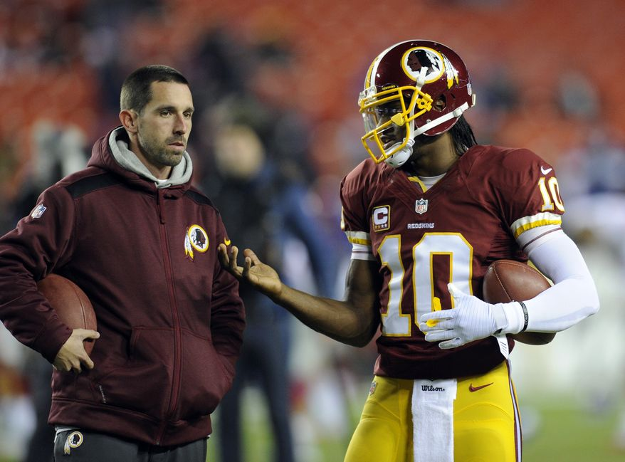 Washington Redskins offensive coordinator Kyle Shanahan, left, talks with quarterback Robert Griffin III during warm ups before an NFL football game against the New York Giants, Sunday, Dec. 1, 2013, in Landover, Md. (AP Photo/Nick Wass)