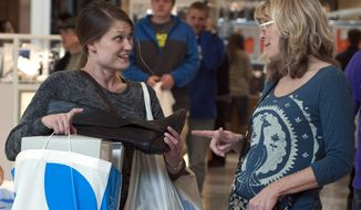 Holiday shoppers Jessica Moe (left) and Teresa Stewart compare notes on a Black Friday bargain at West Town Mall in Knoxville, Tenn., on Friday, Nov. 29, 2013. (AP Photo/The Knoxville News Sentinel, J. Miles Cary)