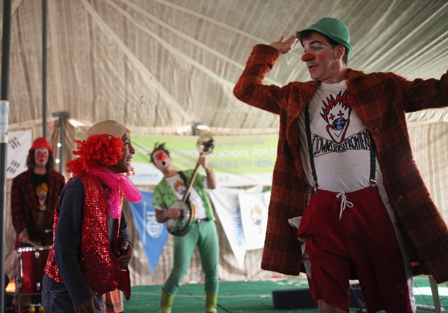 Clowns with the European troupe Mabsutins play music as another clown (Albert Denguito) dresses up a Syrian refugee girl as a clown at the Zaatari refugee camp near the Syrian border in Mafraq, Jordan, on Sunday, Dec. 1, 2013.  (AP Photo/Mohammad Hannon)