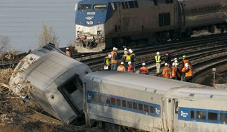 An Amtrak train, top, traveling on an unaffected track, passes a derailed Metro North commuter train, Sunday, Dec. 1, 2013 in the Bronx borough of New York. Officials are standing on a curve in the tracks where the Metro North train derailed. (AP Photo/Mark Lennihan)