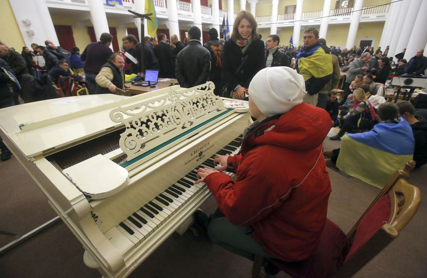 A protester plays the piano in the Kiev city council building which they occupied in downtown Kiev, Ukraine, on Sunday, Dec. 1, 2013. A protest by about 300,000 Ukrainians angered by their government's decision to freeze integration with the West turned violent Sunday, when a group of demonstrators besieged the president's office and police drove them back with truncheons, tear gas and flash grenades. Dozens of people were injured. (AP Photo/Sergei Grits)