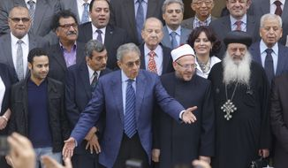 Amr Moussa (center), the chairman of Egypt's 50-member panel tasked with amending the nation's Islamist-drafted constitution, arranges the members for a group picture after finishing the final draft of a series of constitutional amendments at the Shoura Council in Cairo on Monday, Dec. 2, 2013. Adoption of the new charter will be a giant step in the implementation of the road map announced by the nation's military chief when he toppled President Mohammed Morsi in a July 3 coup. The next steps will be parliamentary and presidential elections in the spring and summer of 2014. (AP Photo/Amr Nabil)