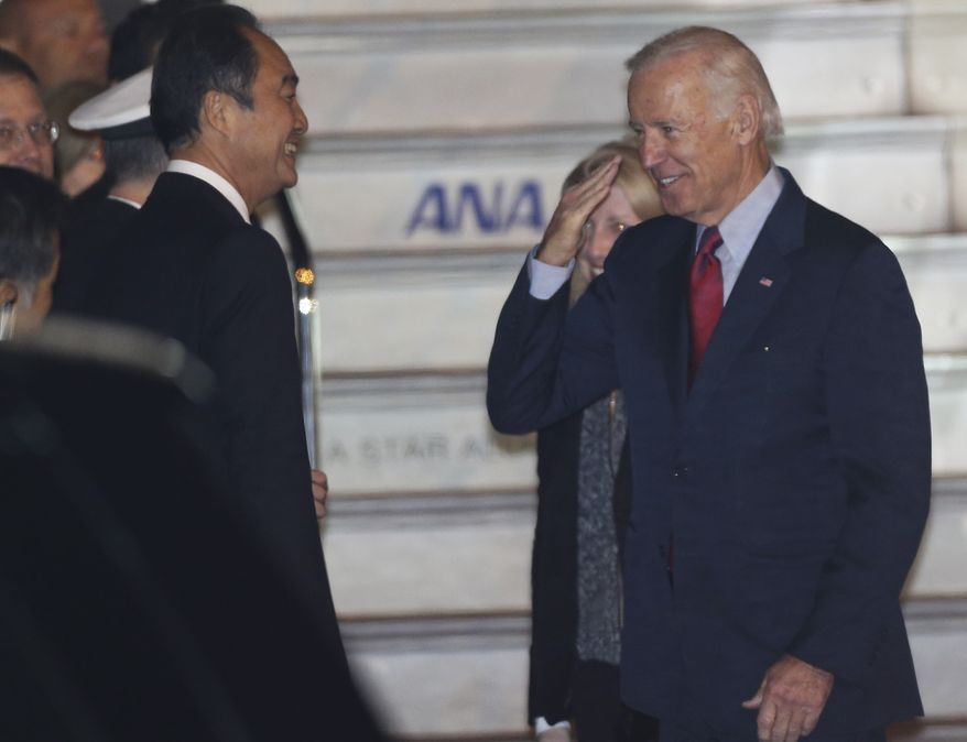 U.S. Vice President Joe Biden salutes upon arriving at the Tokyo International Airport in Tokyo Monday, Dec. 2, 2013. Biden is in Tokyo to meet with Japan's prime minister and lawmakers for the first leg of his Asia tour that includes China and South Korea. (AP Photo/Koji Sasahara)
