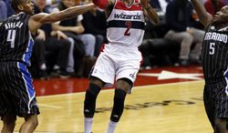 Washington Wizards guard John Wall (2) shoots between Orlando Magic guards Arron Afflalo (4) and Victor Oladipo (5) in the second half of an NBA basketball game Monday, Dec. 2, 2013, in Washington. Wall had 16 points and the Wizards won 98-80. (AP Photo/Alex Brandon)