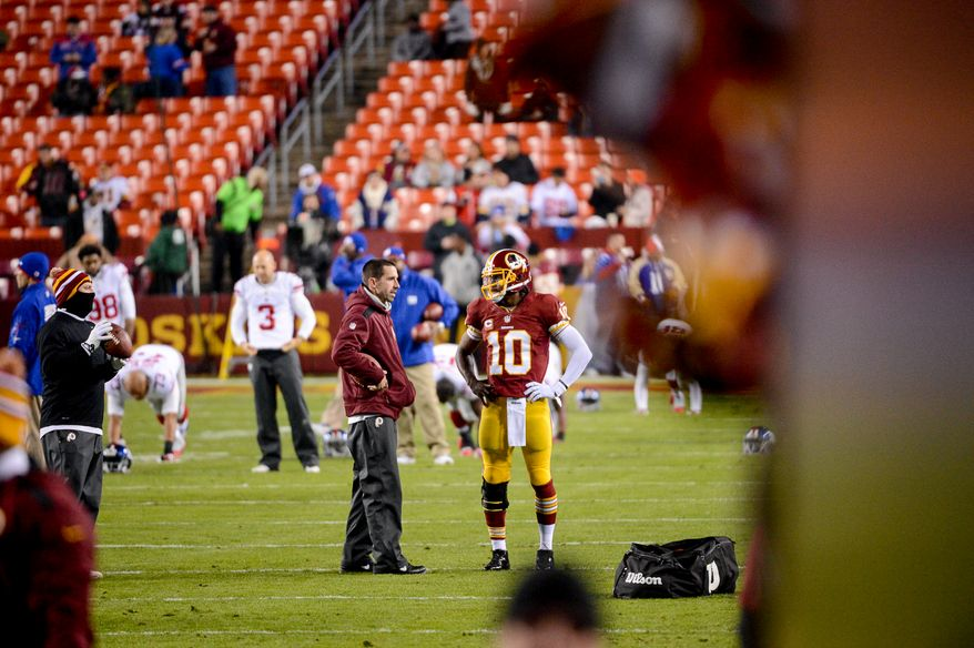 Washington Redskins offensive coordinator Kyle Shanahan talks with Washington Redskins quarterback Robert Griffin III (10) during warmups before the Washington Redskins play the New York Giants in Sunday Night Football at FedExField, Landover, Md., Sunday, December 1, 2013. (Andrew Harnik/The Washington Times)