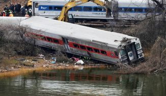 A backhoe clears soil next to a derailed Metro-North commuter train car on Monday, Dec. 2, 2013, in the Bronx borough of New York. In back is a car that had been derailed but was lifted back to the tracks. Federal authorities began righting the cars Monday morning as they started an exhaustive investigation into what caused the train to derail Sunday morning. (Associated Press)
