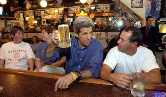 Democratic presidential nominee Sen. John Kerry, D-Mass, has a beer and watches the Green Bay Packers vs. the Indianapolis Colts football game on television during an unscheduled stop inside The Main Street Pub and Grill in Mount Horeb, Wis., Sunday, Sept. 26, 2004. To the right of Kerry is Dan DiMaggio, a patron. (AP Photo/Gerald Herbert)
