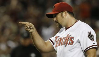 Arizona Diamondbacks' Heath Bell points to catcher Miguel Montero after the final out is recorded against the San Francisco Giants during the ninth inning in a baseball game on Friday, June 7, 2013, in Phoenix.  The Diamondbacks defeated the Giants 3-1. (AP Photo/Ross D. Franklin)