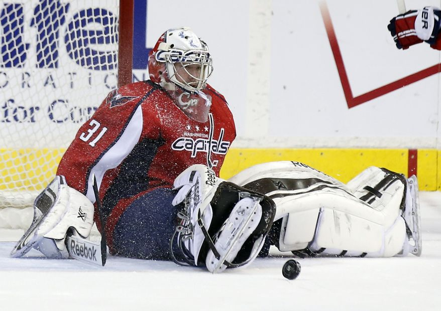 Washington Capitals Philipp Grubauer, from Germany, sits on the ice as the puck bounces nearby in the second period of an NHL hockey game against the Carolina Hurricanes, Tuesday, Dec. 3, 2013, in Washington. The Hurricanes won 4-1. (AP Photo/Alex Brandon)