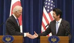"""U.S. Vice President Joe Biden shakes hands with Japanese Prime Minister Shinzo Abe at the end of a joint press conference following their meeting at Abe's official residence in Tokyo Tuesday, Dec. 3, 2013. Biden voiced strong opposition Tuesday to China's new air defense zone above a set of disputed islands, showing a united front with an anxious Japan as tension in the region simmered. Standing side by side in Tokyo with Abe, Biden said the U.S. is """"deeply concerned"""" about China's attempt to unilaterally change the status quo in the East China Sea. (AP Photo/Koji Sasahara)"""