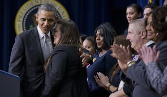 President Barack Obama hugs Monica Weeks, who benefited from the Affordable Care Act by remaining on her parents health care plan while getting treatment for Crohn's disease, after she introduced him to speak about the new health care law, Tuesday, Dec. 3, 2013, in the South Court Auditorium in the Eisenhower Executive Office Building on the White House complex in Washington. The President argued that his health law is preventing insurance discrimination against those with pre-existing conditions and is allowing young people to stay on their parents' coverage until age 26. (AP Photo/ Evan Vucci)