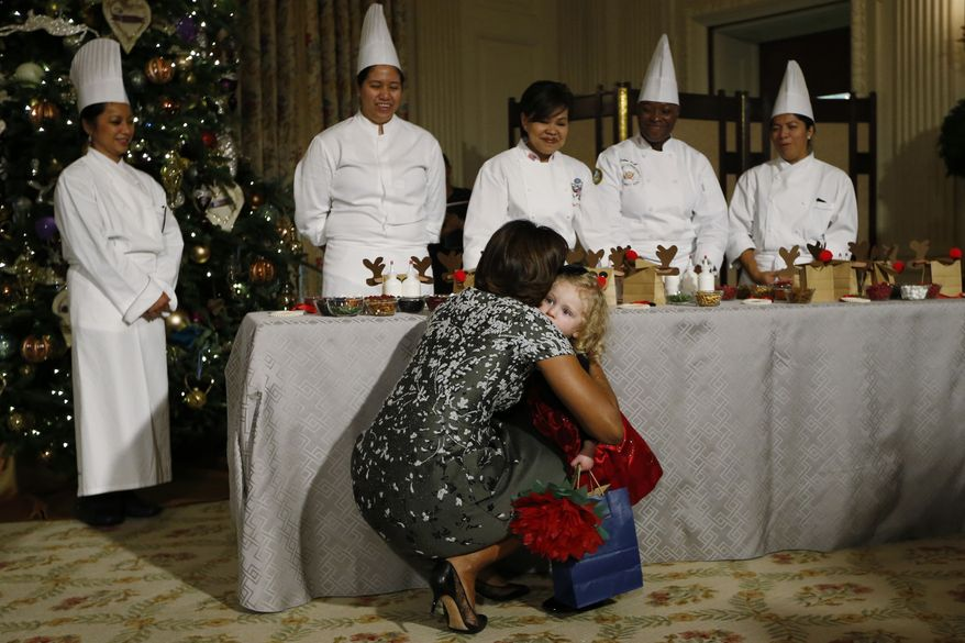 First lady Michelle Obama hugs Ashtyn Gardner, 2, from Mobile, Ala., who earlier lost her balance when she was greeting Sunny, one of the presidential dogs, as children of military families participate in a holiday arts and crafts event in the State Dining Room at the White House in Washington, Wednesday, Dec. 4, 2013. (AP Photo/Charles Dharapak)