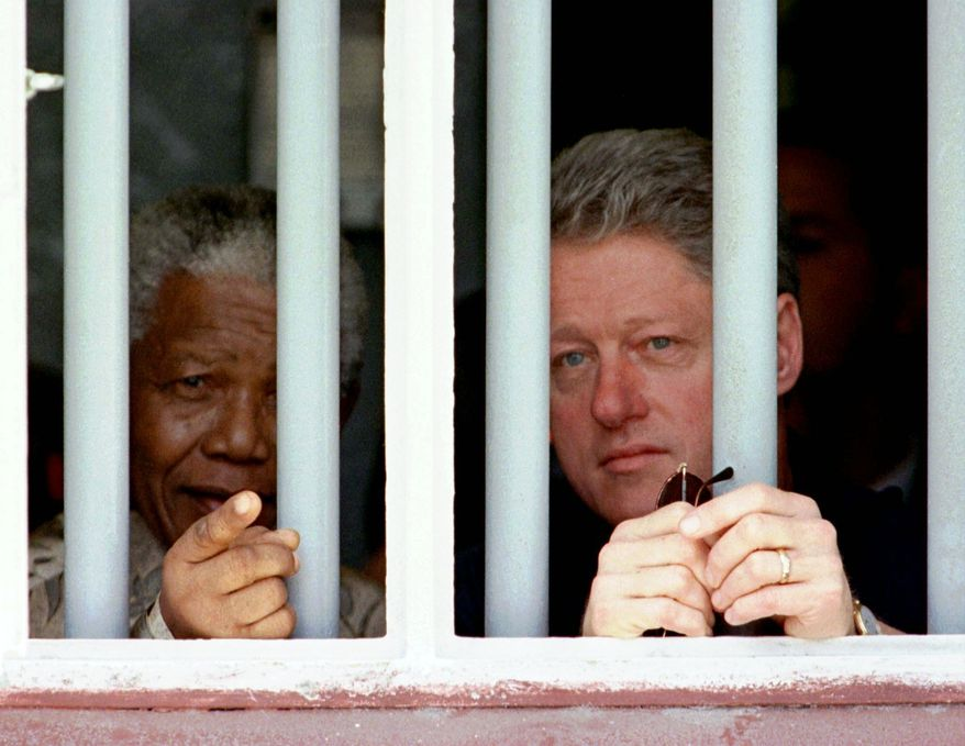 FILE - In this March 27, 1998 file photo, South African President Nelson Mandela, left, and U.S. President Bill Clinton peer through the bars of prison cell No. 5, the cramped, gray cell where Mandela was jailed for 18 years in his struggle against apartheid, on Robben Island, South Africa.  South Africa's president Jacob Zuma says, Thursday, Dec. 5, 2013, that Mandela has died. He was 95.   (AP Photo/Rick Wilking, Pool)