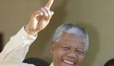 ANC leader Nelson Mandela in a jubilant pose after casting his vote on Wednesday, April 27, 1994 at Ohlange High School hall in Inanda, 10 miles (15 kilometers) north of Durban, for South Africa' s first all-race elections. (AP Photo/Peter Dejong)