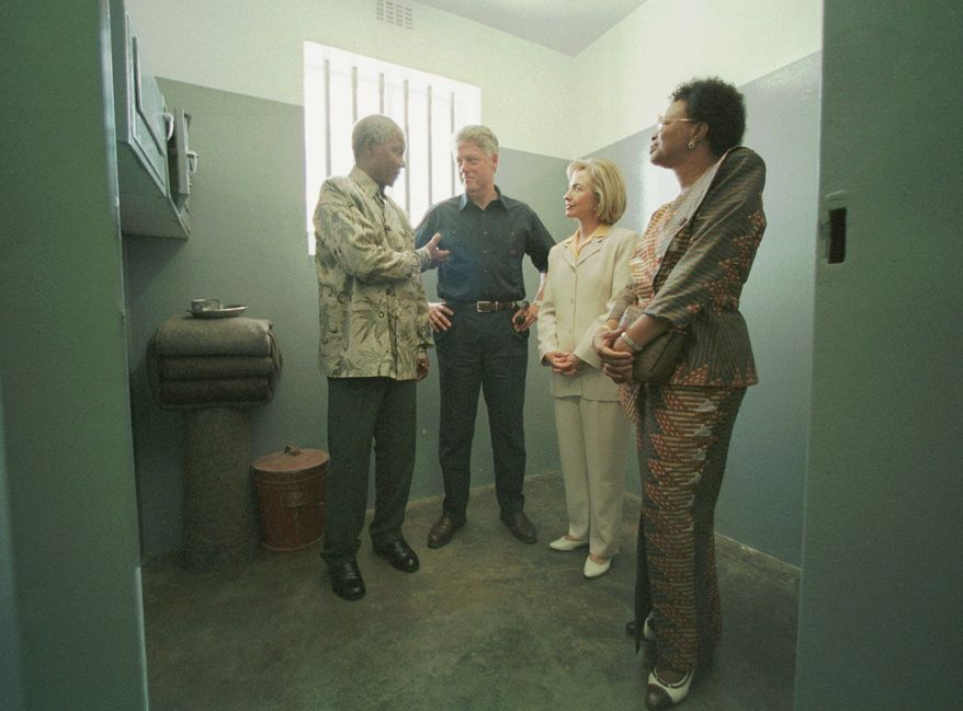 From left, South African President Nelson Mandela, U.S. President Bill Clinton, first lady Hillary Rodham Clinton and Graca Machel, companion of Mandela talk inside the Section B, prison cell No. 5 at the Robben Island, South Africa prison Friday, March 27, 1998. (AP Photo/Pool, J. Scott Applewhite)