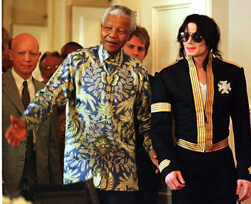 South African President Nelson Mandela, left, and American pop singer Michael Jackson arrive at a news conference in Cape Town Tuesday, March 23, 1999. Jackson announced dates for two concerts in June of which profits will go to various funds including the Nelson Mandela Children's Fund. (AP Photo /Obed Zilwa)