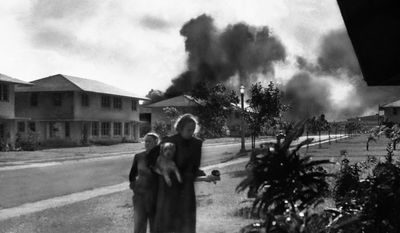 """FILE - In this Dec. 7, 1941 file photo, officers' wives head to their quarters after investigating the sound of an explosion and seeing smoke in distance in Pearl Harbor, Hawaii. The two heard neighbor Mary Naiden, then an Army hostess who took this picture, exclaim """"There are red circles on those planes overhead. They are Japanese!"""" (AP Photo/Mary Naiden)"""