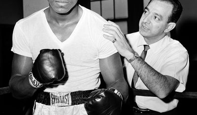 FILE - In this Feb. 8, 1962, file photo, a young Muhammad Ali, left, stands with his trainer Angelo Dundee at City Parks Gym in New York. Dundee, the trainer who helped groom Ali and Sugar Ray Leonard into world champions and became one of boxing's most recognizable figures, died Wednesday, Feb. 1, 2012. He was 90. (AP Photo/Dan Grossi, File)