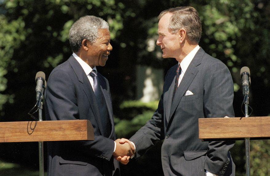 President George Bush shakes hands with South African national leader Nelson Mandela at the White House in Washington, June 25, 1990. (AP Photo/Doug Mills)