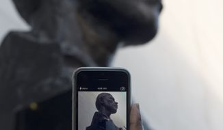 A woman takes a picture on her smartphone of a statue of Nelson Mandela, near the Royal Festival Hall in London, Friday, Dec. 6, 2013. Mandela passed away Thursday night after a long illness. He was 95. As word of Mandela's death spread, current and former presidents, athletes and entertainers, and people around the world spoke about the life and legacy of the former South African leader. (AP Photo/Alastair Grant)