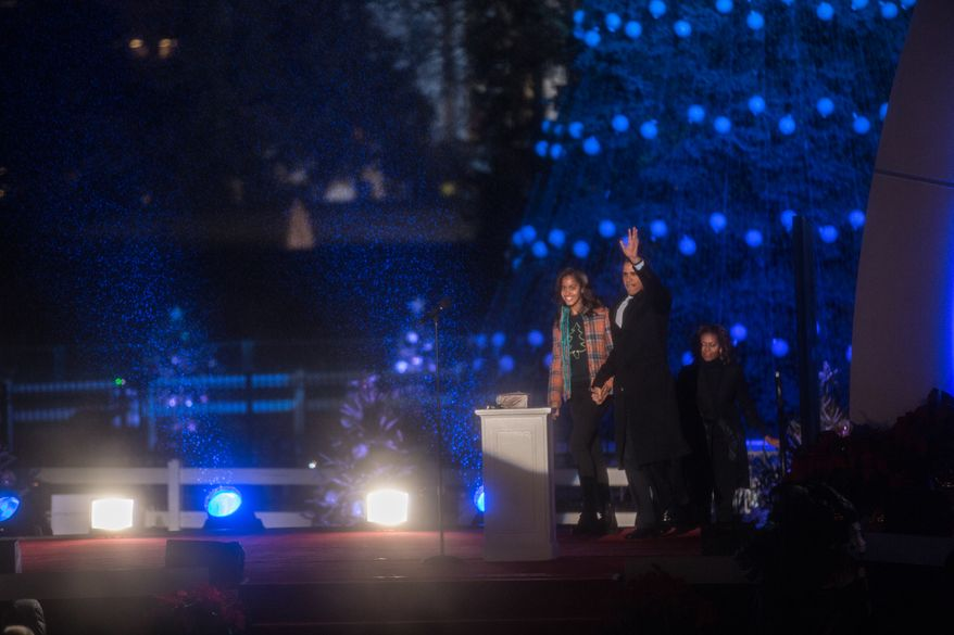 President Obama waves to a wet audience at the start of The National Christmas Tree Lighting held on the south lawn in front of the White House, in Washington, DC., Friday, December 6, 2013.  (Andrew S Geraci/The Washington Times)