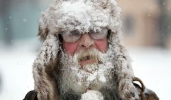 Randy Friedrich of Springfield, Ore. sports a coating of fresh snow as he visits downtown Springfield, Ore. Friday, Dec. 6, 2013. Friedrich, originally from Wisconsin, said he was enjoying the snow day as a storm moves through the Willamette Valley in Oregon (AP Photo/The Register-Guard, Chris Pietsch)