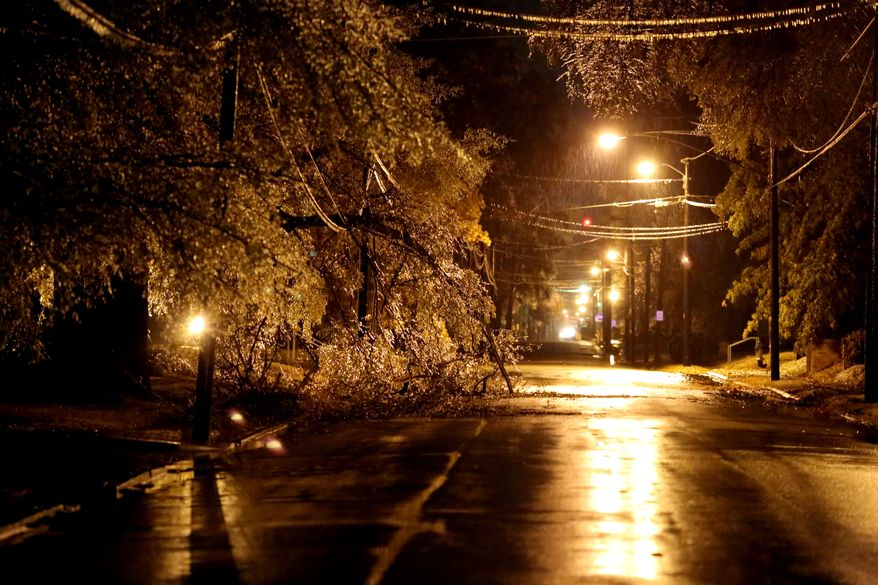 A large limb rests on a power line along in Paris, Texas after breaking away from a tree due to heavy ice accumulation.  A winter storm moved into North East Texas Friday, Dec. 6, 2013 bringing with it freezing rain, ice and temperatures in the low 20's.  (AP Photo / The Paris News, Sam Craft)