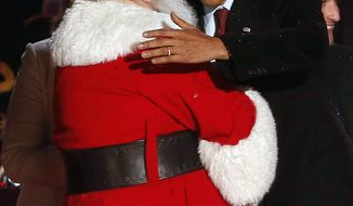 President Barack Obama hugs Santa at the National Christmas Tree lighting ceremony across from the White House in Washington, Friday, Dec. 6, 2013. (AP Photo/Charles Dharapak)