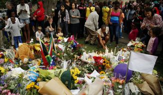 A group of mourners stand around floral tributes laid in memory of former president Nelson Mandela's home in Johannesburg, South Africa, Friday, Dec. 6, 2013, after he passed away Thursday night following a long illness. (AP Photo/Themba Hadebe)