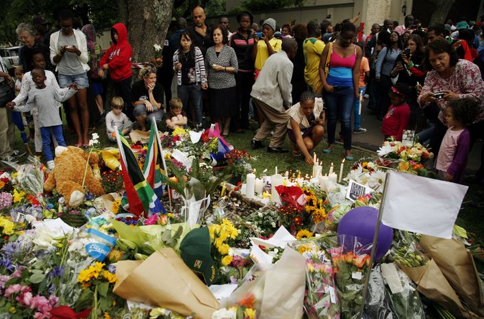 A group of mourners stand around floral tributes laid in memory of former president Nelson Mandela's home in Johannesburg, South Africa, Friday, Dec. 6, 2013, after he passed away Thursday