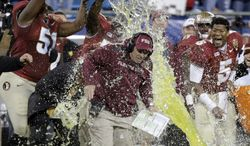 Florida State head coach Jimbo Fisher, center, is dunked by Bobby Hart, left as Jameis Winston, right, laughs in the second half of the Atlantic Coast Conference Championship NCAA football game in Charlotte, N.C., Saturday, Dec. 7, 2013. Florida State won 44-7.  (AP Photo/Chuck Burton)