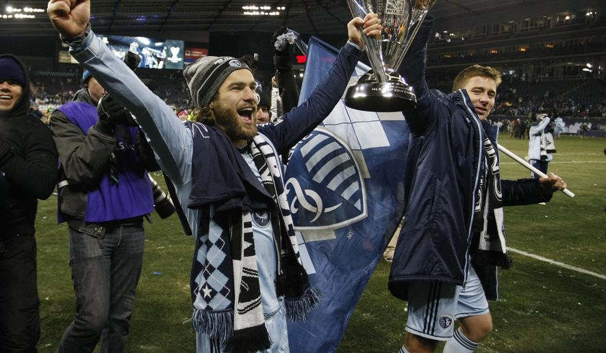 Sporting Kansas City's Graham Zusi, left, and Matt Besler, right, celebrate as they carry the MLS Cup after their 2-1 win over Real Salt Lake in the MLS Cup soccer final match in Kansas City, Kan., Saturday, Dec. 7, 2013. (AP Photo/Colin E. Braley)
