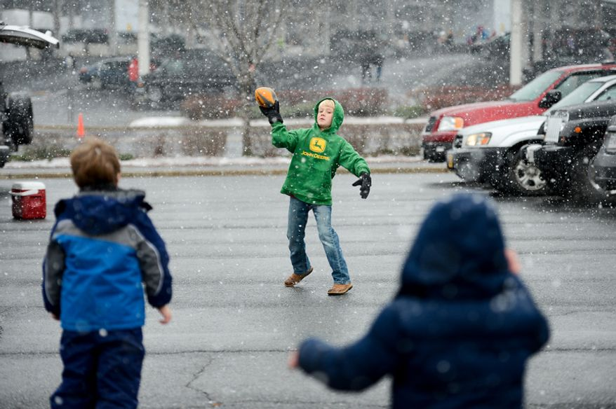 George Sobba (center), 7, of Arlington, Va., throws a football in the parking lot of FedEx Field in Landover, Md., as the Washington Redskins get set to play the Kansas City Chiefs in snowy conditions on Sunday, Dec. 8, 2013. (Andrew Harnik/The Washington Times)