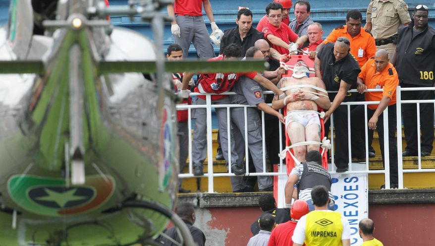 An injured fan is carried on a stretcher after clashes with team fans during a Brazilian league soccer match between Atletico Paranaense and Vasco da Gama in Joinville, southern Brazil, Sunday, Dec. 8, 2013. A key Brazilian league match was stopped Sunday after fans started fighting in the stands and a helicopter had to land on the pitch to airlift a seriously injured man. A doctor said two other fans were hospitalized in serious condition and one was treated for a minor injury at the stadium. (AP Photo/Carlos Moraes, Agencia O Dia)