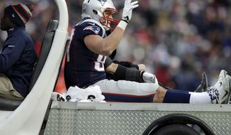 New England Patriots tight end Rob Gronkowski waves as he leaves the field in a cart after being injured in the third quarter of an NFL football game against the Cleveland Browns Sunday, Dec. 8, 2013, in Foxborough, Mass.  (AP Photo/Steven Senne)