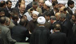 In this photo released by the official website of the office of the Iranian Presidency, Iran's President Hassan Rouhani, center, is surrounded by lawmakers during an open session of parliament to submit next year's budget bill, in Tehran, Iran, Sunday, Dec. 8, 2013. Rouhani said Sunday that last month's nuclear deal with world powers has already boosted the country's economy, as he continues a push to convince skeptics of the benefits brought by the pact's partial sanctions relief.  The proposed budget covers Iran's fiscal year that starts March 21, 2014. (AP Photo/Presidency Office, Rouzbeh Jadidoleslam)